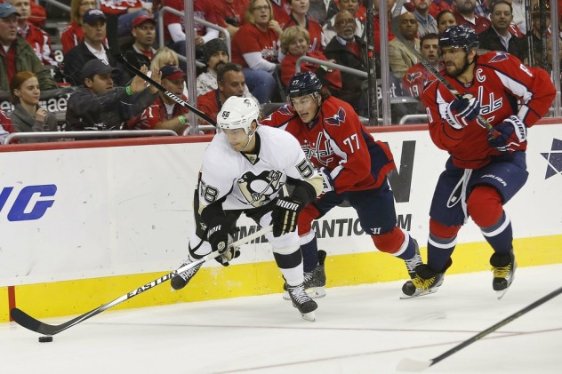 Oct 28, 2015; Washington, DC, USA; Pittsburgh Penguins defenseman Kris Letang (58) skates with the puck as Washington Capitals right wing T.J. Oshie (77) chases in the first period at Verizon Center. Mandatory Credit: Geoff Burke-USA TODAY Sports
