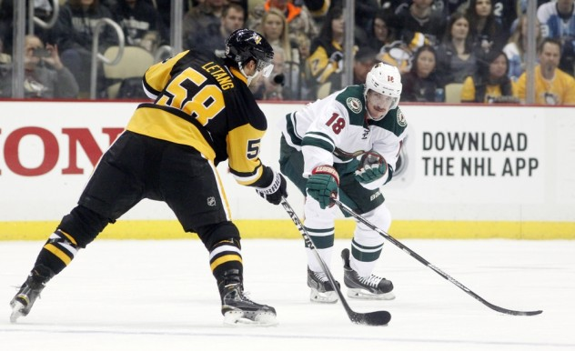 Nov 17, 2015; Pittsburgh, PA, USA; Pittsburgh Penguins defenseman Kris Letang (58) shoots the puck as Minnesota Wild center Ryan Carter (18) defends during the third period at the CONSOL Energy Center. The Penguins won 4-3. Mandatory Credit: Charles LeClaire-USA TODAY Sports