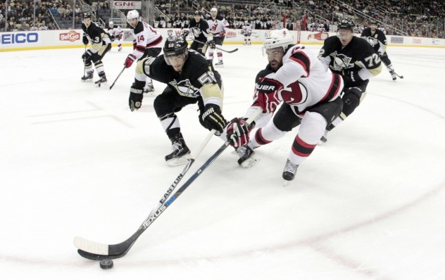 Jan 26, 2016; Pittsburgh, PA, USA; Pittsburgh Penguins defenseman Kris Letang (58) and New Jersey Devils right wing Kyle Palmieri (21) reach for the puck during the third period at the CONSOL Energy Center. The Penguins won 2-0. Mandatory Credit: Charles LeClaire-USA TODAY Sports