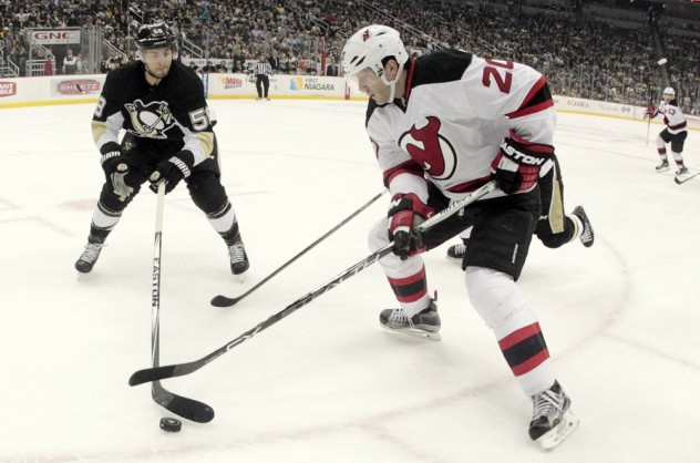 Jan 26, 2016; Pittsburgh, PA, USA; Pittsburgh Penguins defenseman Kris Letang (58) and New Jersey Devils right wing Lee Stempniak (20) reach for the puck during the first period at the CONSOL Energy Center. The Penguins won 2-0. Mandatory Credit: Charles LeClaire-USA TODAY Sports