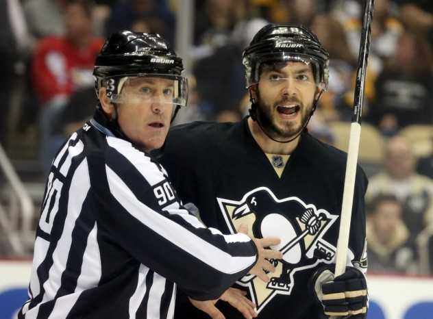 Feb 20, 2016; Pittsburgh, PA, USA; Pittsburgh Penguins defenseman Kris Letang (58) reacts while being restrained by linesman Andy McElman (90) against the Tampa Bay Lightning during the first period at the CONSOL Energy Center. Mandatory Credit: Charles LeClaire-USA TODAY Sports