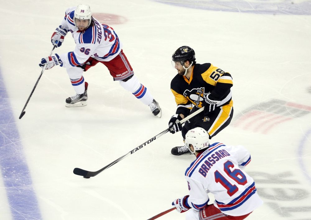 Apr 13, 2016; Pittsburgh, PA, USA; Pittsburgh Penguins defenseman Kris Letang (58) skates with the puck between New York Rangers right wing Mats Zuccarello (36) and center Derick Brassard (16) during the second period in game one of the first round of the 2016 Stanley Cup Playoffs at the CONSOL Energy Center. Mandatory Credit: Charles LeClaire-USA TODAY Sports