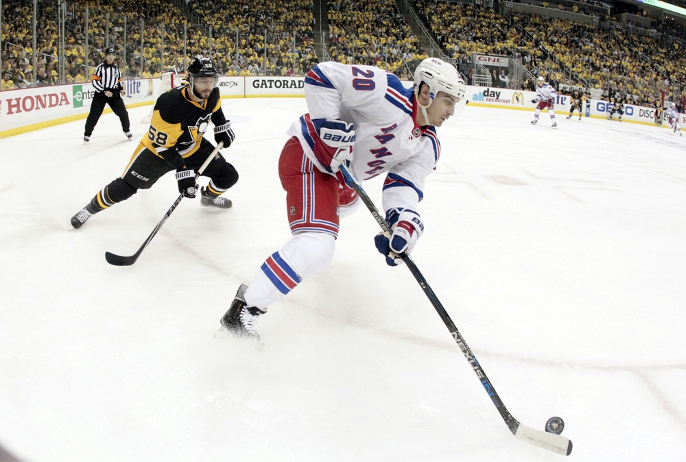 Apr 13, 2016; Pittsburgh, PA, USA; New York Rangers left wing Chris Kreider (20) moves the puck ahead of Pittsburgh Penguins defenseman Kris Letang (58) during the first period in game one of the first round of the 2016 Stanley Cup Playoffs at the CONSOL Energy Center. Mandatory Credit: Charles LeClaire-USA TODAY Sports
