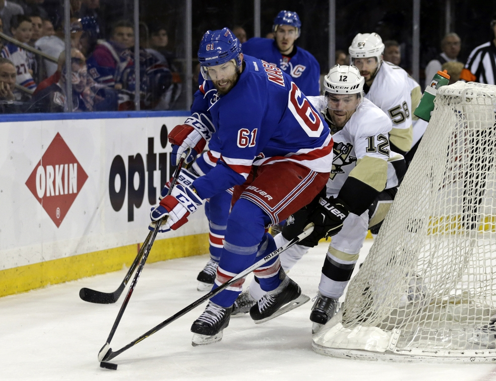 Apr 21, 2016; New York, NY, USA; New York Rangers left wing Rick Nash (61) has the puck knocked away by Pittsburgh Penguins defenseman Ben Lovejoy (12) during the second period in game four of the first round of the 2016 Stanley Cup Playoffs at Madison Square Garden. Mandatory Credit: Adam Hunger-USA TODAY Sports
