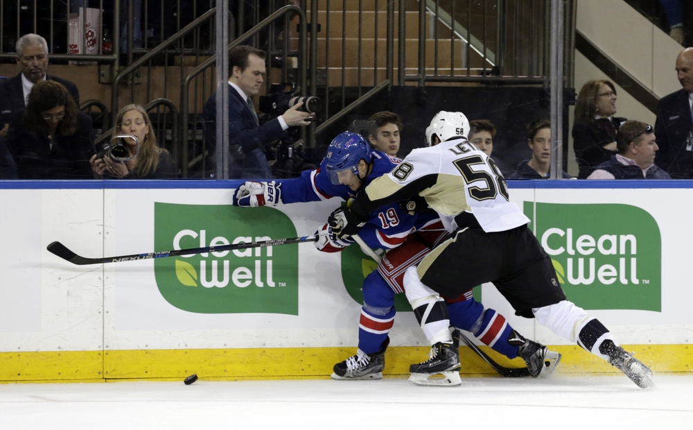 Apr 21, 2016; New York, NY, USA; Pittsburgh Penguins defenseman Kris Letang (58) and New York Rangers right wing Jesper Fast (19) battle for puck during the second period in game four of the first round of the 2016 Stanley Cup Playoffs at Madison Square Garden. Mandatory Credit: Adam Hunger-USA TODAY Sports