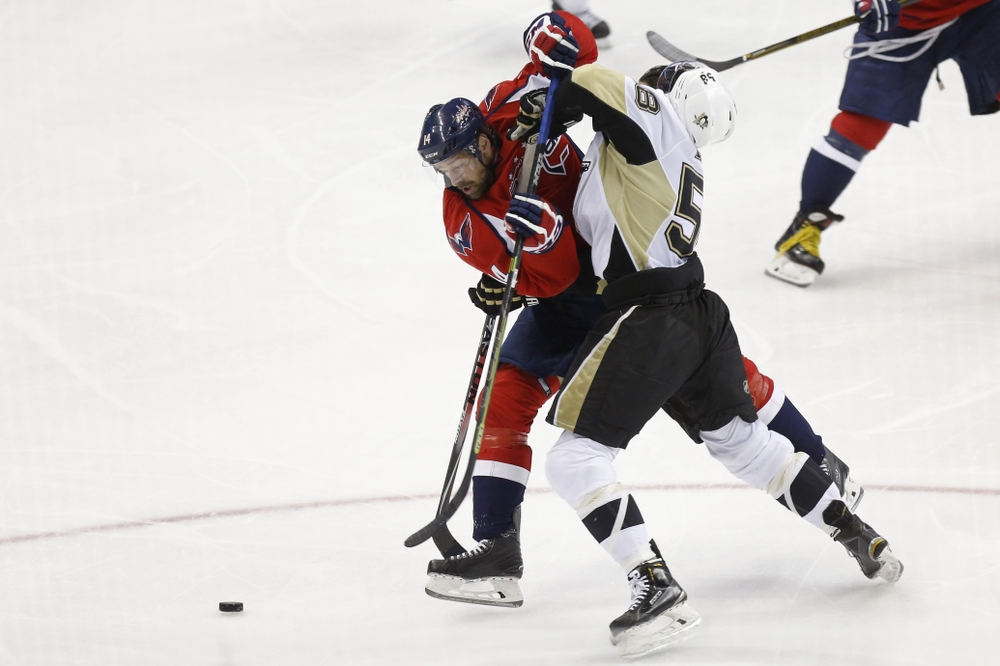 Apr 30, 2016; Washington, DC, USA; Washington Capitals right wing Justin Williams (14) and Pittsburgh Penguins defenseman Kris Letang (58) battle for the puck in the third period in game two of the second round of the 2016 Stanley Cup Playoffs at Verizon Center. The Penguins won 2-1, and the series is tied 1-1. Mandatory Credit: Geoff Burke-USA TODAY Sports