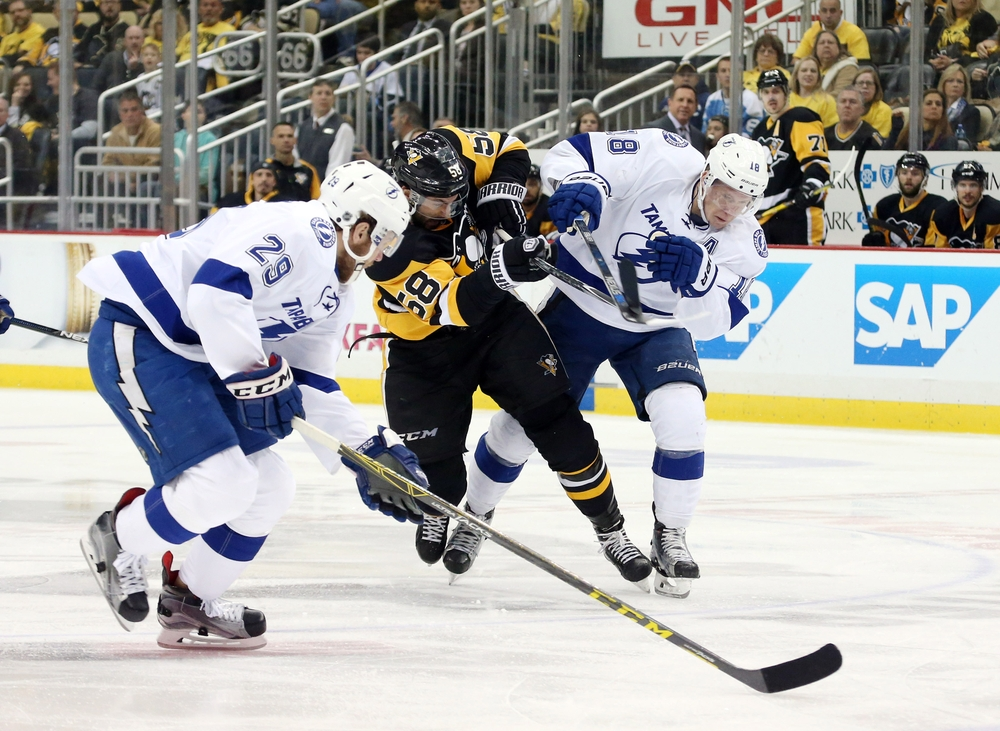 May 16, 2016; Pittsburgh, PA, USA; Pittsburgh Penguins defenseman Kris Letang (58) shoots between Tampa Bay Lightning defenseman Slater Koekkoek (29) and left wing Ondrej Palat (18) during the third period in game two of the Eastern Conference Final of the 2016 Stanley Cup Playoffs at the CONSOL Energy Center. The Penguins won 3-2 in overtime to even the series 1 game to 1. Mandatory Credit: Charles LeClaire-USA TODAY Sports