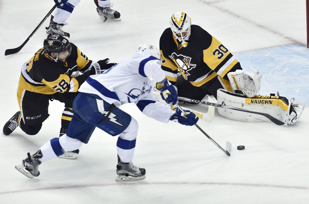 May 16, 2016; Pittsburgh, PA, USA; Pittsburgh Penguins defenseman Kris Letang (58) defends as Matt Murray (30) makes a save against Tampa Bay Lightning left wing Ondrej Palat (18) during the third period in game two of the Eastern Conference Final of the 2016 Stanley Cup Playoffs at Consol Energy Center. Mandatory Credit: Don Wright-USA TODAY Sports