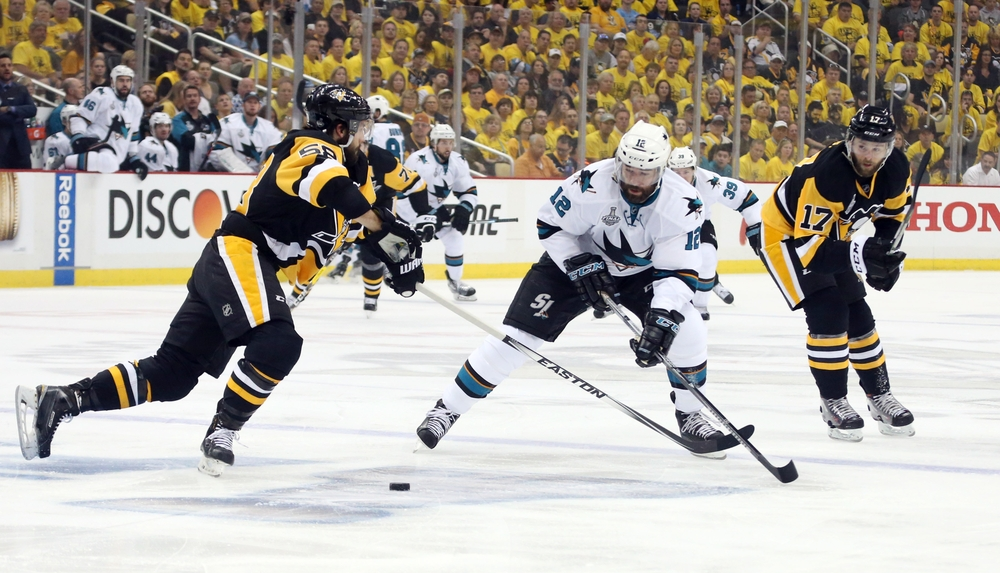 May 30, 2016; Pittsburgh, PA, USA; San Jose Sharks center Patrick Marleau (12) battles for the puck between Pittsburgh Penguins defenseman Kris Letang (58) and right wing Bryan Rust (17) in the first period game one of the 2016 Stanley Cup Final at Consol Energy Center. Mandatory Credit: Charles LeClaire-USA TODAY Sports
