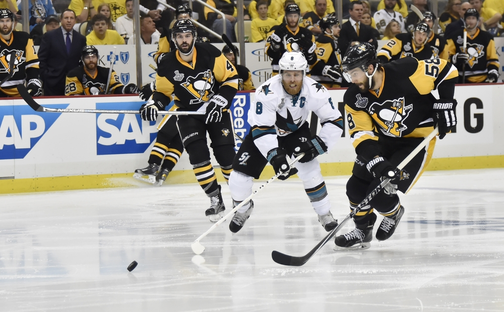 May 30, 2016; Pittsburgh, PA, USA; Pittsburgh Penguins defenseman Kris Letang (58) chases after the puck with San Jose Sharks center Joe Pavelski (8) in the third period in game one of the 2016 Stanley Cup Final at Consol Energy Center. Mandatory Credit: Don Wright-USA TODAY Sports