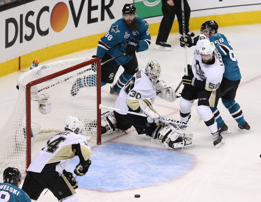 Jun 6, 2016; San Jose, CA, USA; The puck moves through the crease and by Pittsburgh Penguins goalie Matt Murray (30) as Pittsburgh Penguins defenseman Kris Letang (58) ties up San Jose Sharks right wing Melker Karlsson (68) in the second period in game four of the 2016 Stanley Cup Final at SAP Center at San Jose. Mandatory Credit: John Hefti-USA TODAY Sports