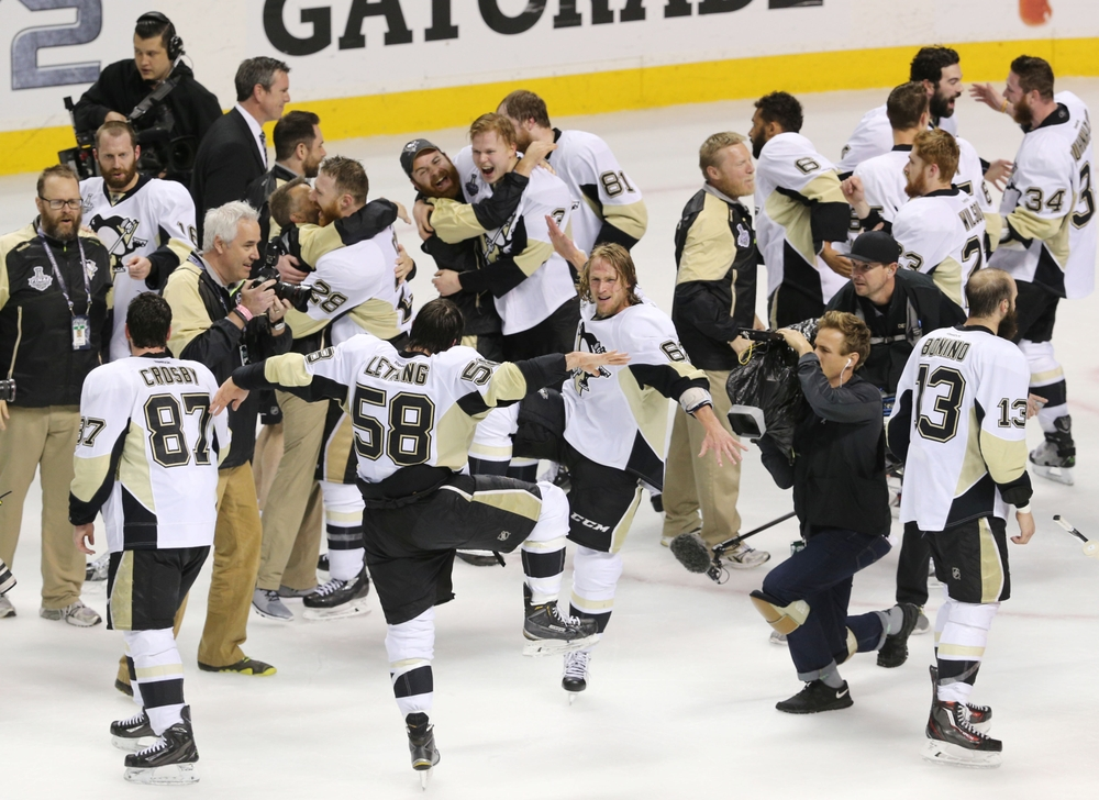 Jun 12, 2016; San Jose, CA, USA; Pittsburgh Penguins players including defenseman Kris Letang (58) and left wing Carl Hagelin (62) celebrate after defeating the San Jose Sharks in game six of the 2016 Stanley Cup Final at SAP Center at San Jose. Mandatory Credit: John Hefti-USA TODAY Sports