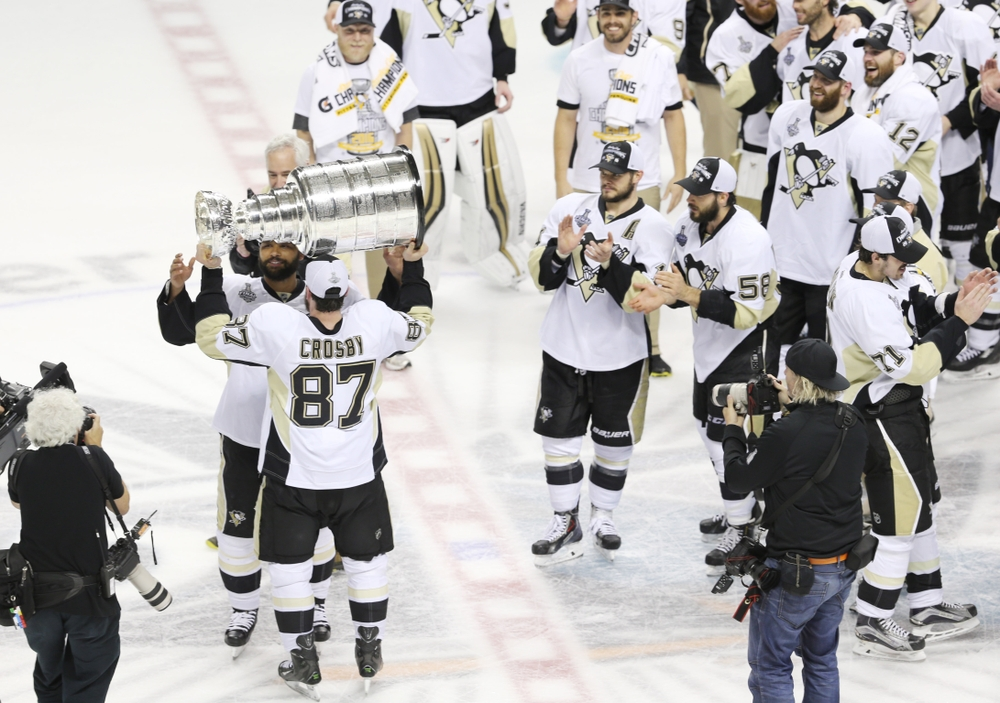Jun 12, 2016; San Jose, CA, USA; Pittsburgh Penguins center Sidney Crosby (87) passes the Stanley Cup to defenseman Trevor Daley (6) after defeating the San Jose Sharks in game six of the 2016 Stanley Cup Final at SAP Center at San Jose. Mandatory Credit: Gary A. Vasquez-USA TODAY Sports