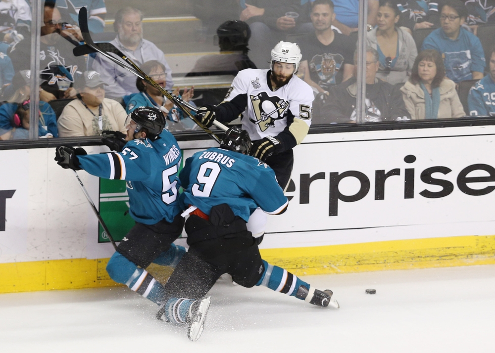 Jun 12, 2016; San Jose, CA, USA; San Jose Sharks right wing Dainius Zubrus (9) crashes into center Tommy Wingels (57) while chasing the puck against Pittsburgh Penguins defenseman Kris Letang (58) in the first period of game six of the 2016 Stanley Cup Final at SAP Center at San Jose. Mandatory Credit: John Hefti-USA TODAY Sports