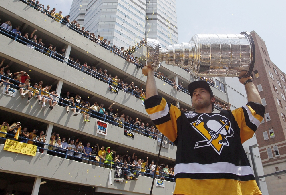 Jun 15, 2016; Pittsburgh, PA, USA; Fans look on from a parking garage as Pittsburgh Penguins defenseman Kris Letang (58) carries the cup during the Stanley Cup championship parade and celebration in downtown Pittsburgh. Mandatory Credit: Charles LeClaire-USA TODAY Sports
