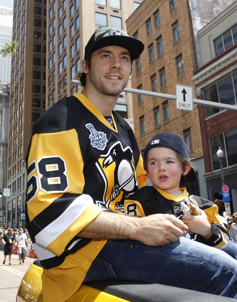 Jun 15, 2016; Pittsburgh, PA, USA; Pittsburgh Penguins defenseman Kris Letang (58) and son Alex Letang participate during the Stanley Cup championship parade and celebration in downtown Pittsburgh. Mandatory Credit: Charles LeClaire-USA TODAY Sports