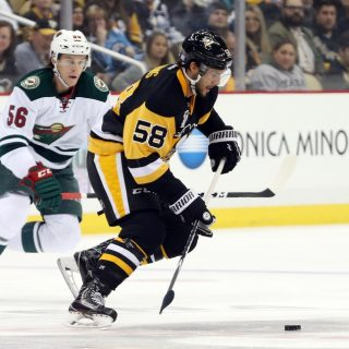 Nov 10, 2016; Pittsburgh, PA, USA;  Pittsburgh Penguins defenseman Kris Letang (58) moves the puck as Minnesota Wild center Erik Haula (56) defends during the first period at the PPG Paints Arena. Mandatory Credit: Charles LeClaire-USA TODAY Sports