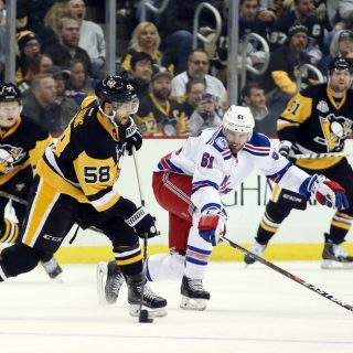 Nov 21, 2016; Pittsburgh, PA, USA;  Pittsburgh Penguins defenseman Kris Letang (58) shoots the puck as New York Rangers right wing Rick Nash (61) defends during the third period at the PPG Paints Arena. The Rangers won 5-2. Mandatory Credit: Charles LeClaire-USA TODAY Sports