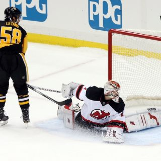 Nov 26, 2016; Pittsburgh, PA, USA;  Pittsburgh Penguins defenseman Kris Letang (58) scores a goal past New Jersey Devils goalie Keith Kinkaid (1) in the shootout at the PPG PAINTS Arena. The Pens won 4-3 in a shootout. Mandatory Credit: Charles LeClaire-USA TODAY Sports