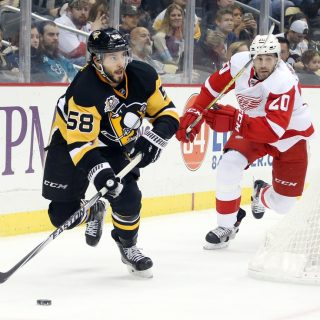 Dec 3, 2016; Pittsburgh, PA, USA;  Pittsburgh Penguins defenseman Kris Letang (58) clears the puck ahead of Detroit Red Wings left wing Drew Miller (20) during the third period at the PPG PAINTS Arena. Pittsburgh won 5-3. Mandatory Credit: Charles LeClaire-USA TODAY Sports