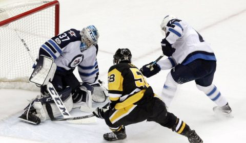 Feb 16, 2017; Pittsburgh, PA, USA; Winnipeg Jets goalie Connor Hellebuyck (37) makes a save against Pittsburgh Penguins defenseman Kris Letang (58) in overtime at the PPG PAINTS Arena. The Penguins won 4-3 in overtime. Mandatory Credit: Charles LeClaire-USA TODAY Sports